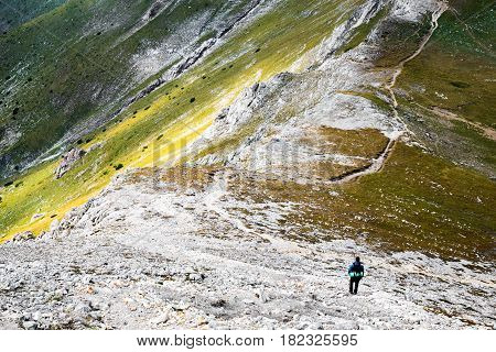 Hiker with backpack in distance on picturesque highland landscape standing on curvy trail over steep mountain shot from above. Pirin mountain under the peak Vihren Bulgaria