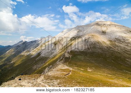 View from under the peak Vihren to the marble part of Pirin mountain Bulgaria. Hiker resting after long walk over steep mountain range.