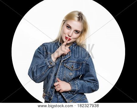 young blonde woman in denim jaket and jeans shows Index finger to the lips on white background. White circle on a black background