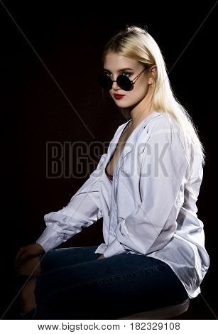 Pretty blond girl in a man's shirt and sunglasses posing on a dark background.