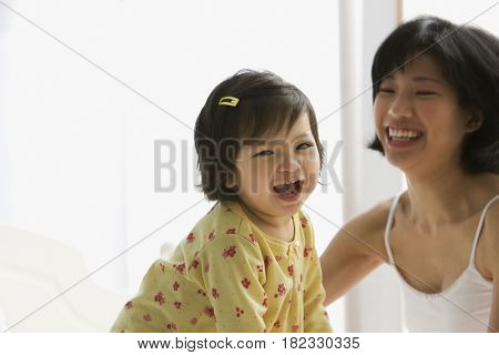 Mixed race girl laughing with mother