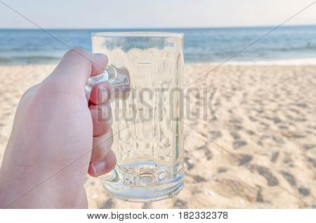 Empty mug of drained fresh beer on the beach