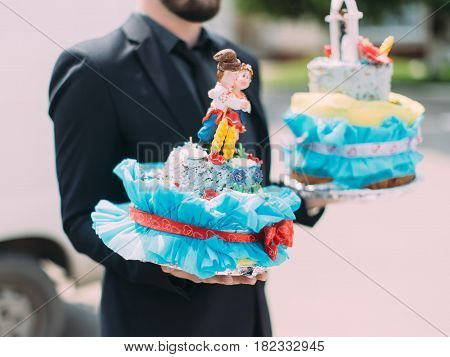 The side view of the wedding cake with decorations carried by the man