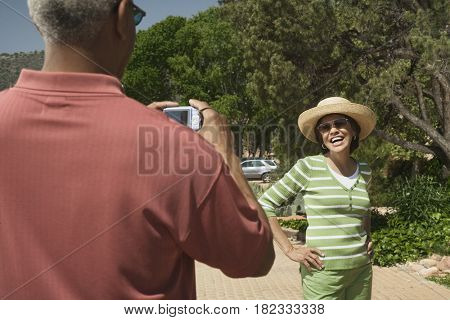 African man taking photograph of wife