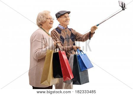 Cheerful senior couple with shopping bags taking a selfie with a stick isolated on white background