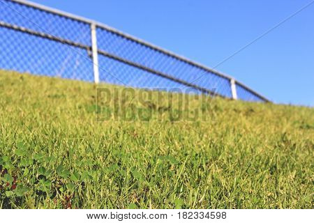 Grassy Hill with soft focus rail and Blue sky