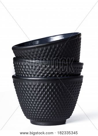 Stacked black traditional tea cups of cast iron isolated on white background.