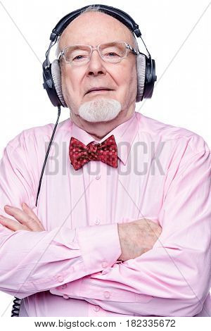 Portrait of a handsome old man listening to music in headphones. Isolated over white.
