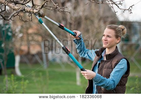 Girl gardener working in the spring garden and trimming tree