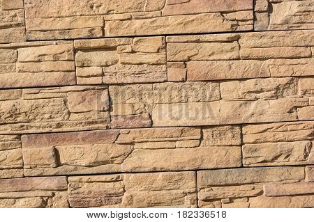 Close up beige stone wall formed from flat layered rocks