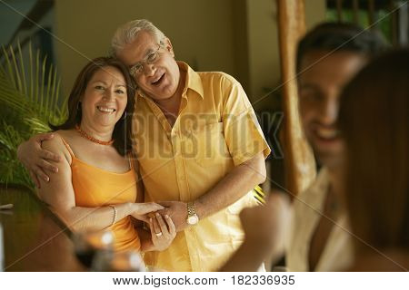 Hispanic couple hugging and smiling
