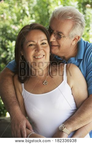 Hispanic couple smiling and hugging