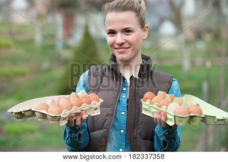 Smiling young woman holding Fresh chicken eggs in hands outdoors