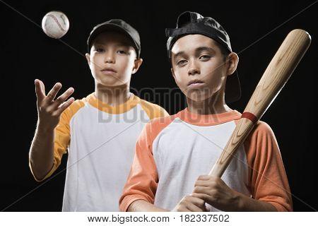 Boys holding bat and throwing baseball