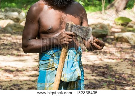 Close up of Vedda man holding axe