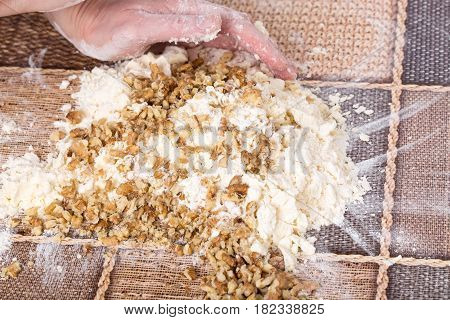 Male hands making dough with walnuts and grated butter on a table as a background.