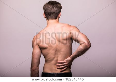 Man Rubbing His Painful Back On Grey . Pain Relief, Chiropractic Concept