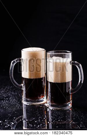 Two mugs of foamy beer on black background