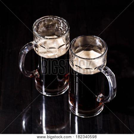 Two mugs of beer on blank black table
