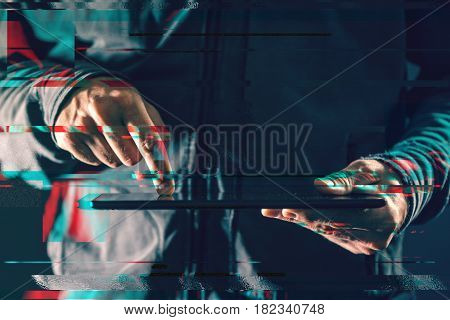Digital tablet computer in male hands in dark room glitch effect low key close up