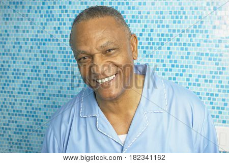 African man in pajamas smiling in bathroom