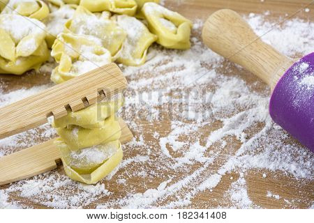 Ravioli on the wooden table with flour and plunger