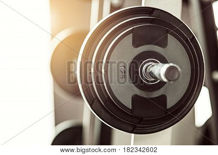 Close up view of barbell on floor in gym at sunny day
