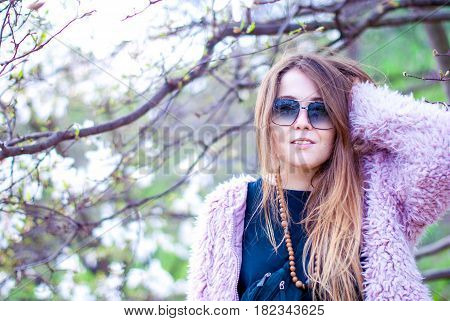 Happy girl in an artificial pink coat. Beautiful woman with long hair. The girl smiles In an artificial fur coat and sunglasses in the magnolia garden.