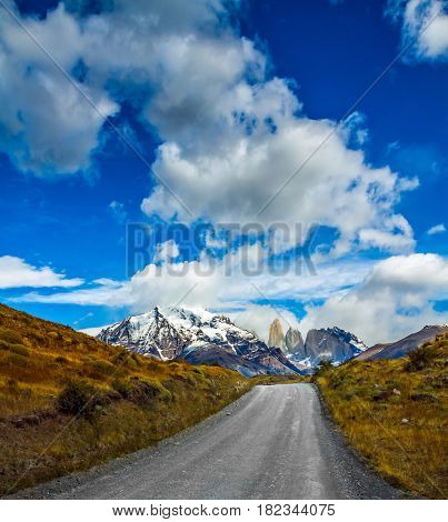 Concept of automobile extreme tourism. The gravel road in national park Torres del Paine. Mountains and rocks Torres are covered with snow and ice