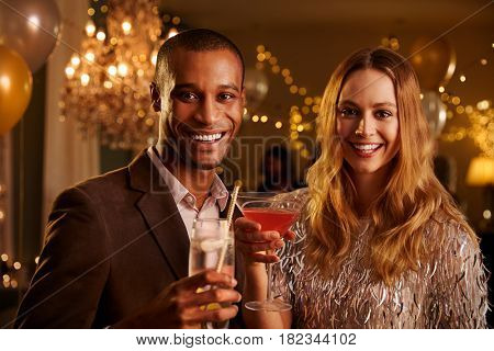 Portrait Of Couple With Drinks Enjoying Cocktail Party