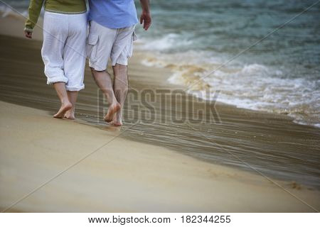 Hispanic couple walking on beach