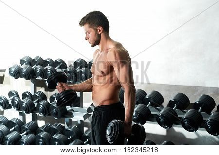 Healthy young man doing weightlifting workout with dumbbells at the local gym copyspace fitness sport people lifestyle motivation youth physical activity sportsperson concept.