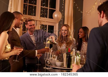 Man Making Cocktails For Friends At Party