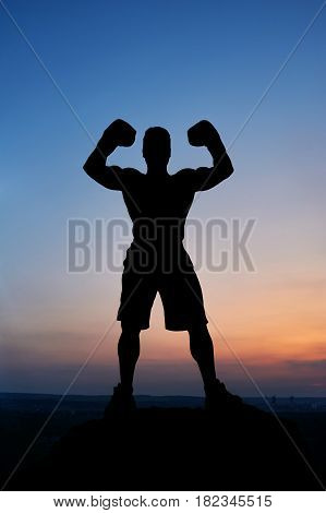 Silhouette of a muscular strong man flexing his muscles standing outdoors stunning sunset scenery on the background guy mysterious incognito sportsperson sportsman boxer fighter bodybuilder