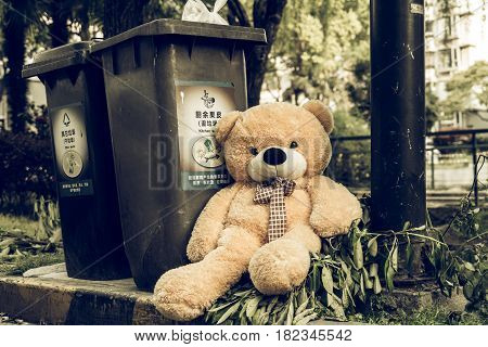 The teddy-bear was throw away sitting byside the garbage trash