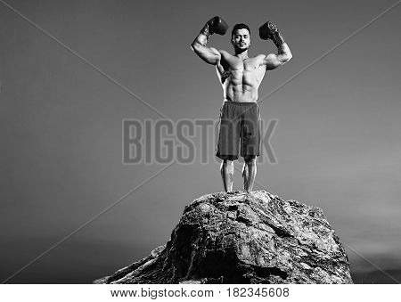 Horizontal full length black and white shot of a strong muscular boxer flexing his muscles posing outdoors copyspace boxing fighter fighting masculinity strength power confidence fitness sport.
