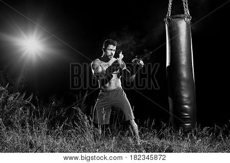 Monochrome portrait of a focused male boxer exercising outdoors hitting a punching bag wearing burning boxing gloves copyspace concentration determination fit toned body torso strengthening concept.