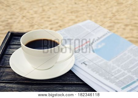Close up white coffee cup on wood table at sunrise sand beach with newspaper in the morning warm tone Thailand