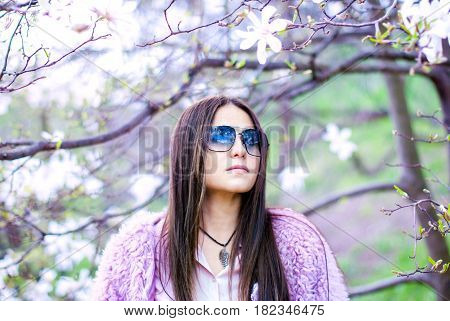 Beautiful girl with long hair wearing sunglasses. Beautiful woman in a fur coat. Calm girl in a blooming garden. Young woman in a pink fur coat.