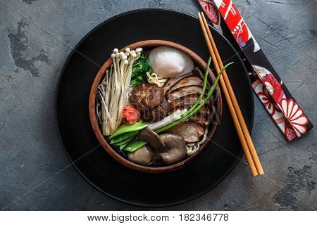 Ramen noodles with duck, egg, enoki and shiitake mushrooms with broth on dark background, top view