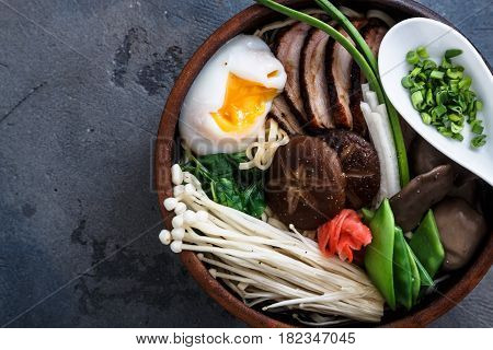 Ramen noodles bowl with egg, enoki, shiitake mushrooms, duck and onion, dark background, close view
