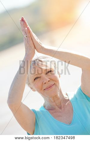 Senior blond woman doing yoga exercices on the beach