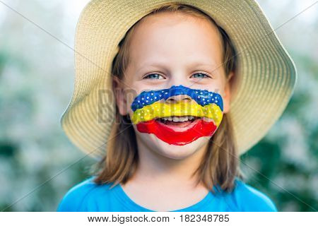 Laughing Little Girl In Straw Hat With Painted Face Having Fun. Outdoor Portrait