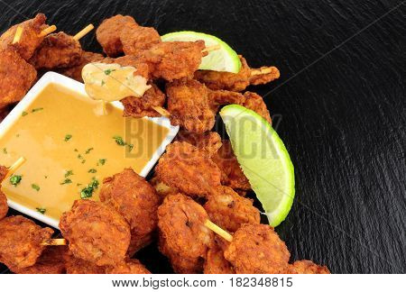 Chicken satay skewers with peanut sauce dip on a slate background