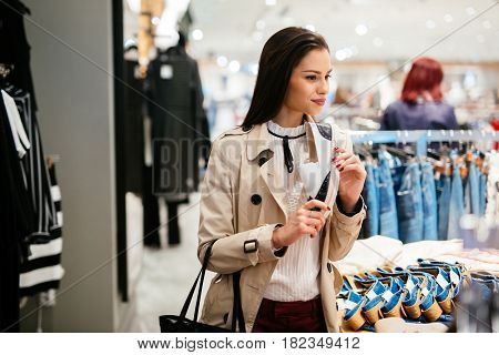 Pretty young woman shopping trendy footware in shop