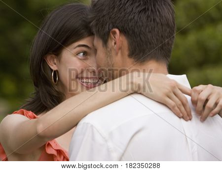 Multi-ethnic couple hugging outdoors