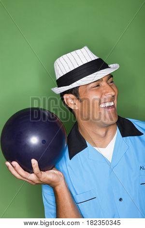 Hispanic man holding bowling ball