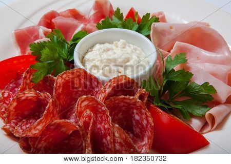 Cold Smoked Meat Plate With Prosciutto, Salami, Bacon, Ham And Sauce On A White Plate.