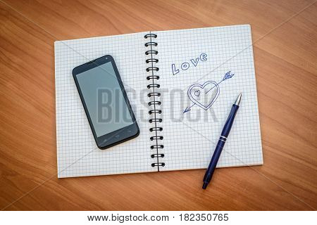 Drawn with a ballpoint pen heart with an arrow and the word LOVE in the open notebook with mobile phone and pen