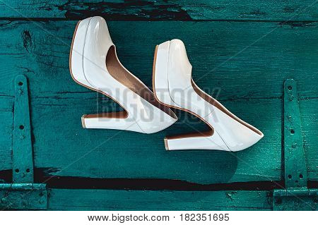 bride's biege shoes on heel on a wooden board tiffany colour.